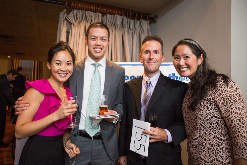 Guests, including Board Member Edward W. Chang (second from left) bid on gift packages throughout the night as part of the fundraiser.