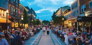 State Street in Media, PA; closed to auto traffic with dining tables out in the street in the early evening. Two pedestrians can be seen walking down the trolley tracks, which are kept open for walking
