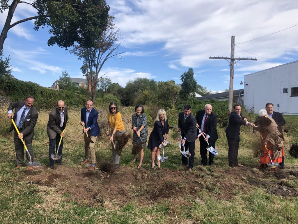 A line of local electeds and nonprofit leaders churn some dirt with ceremonial shovels.